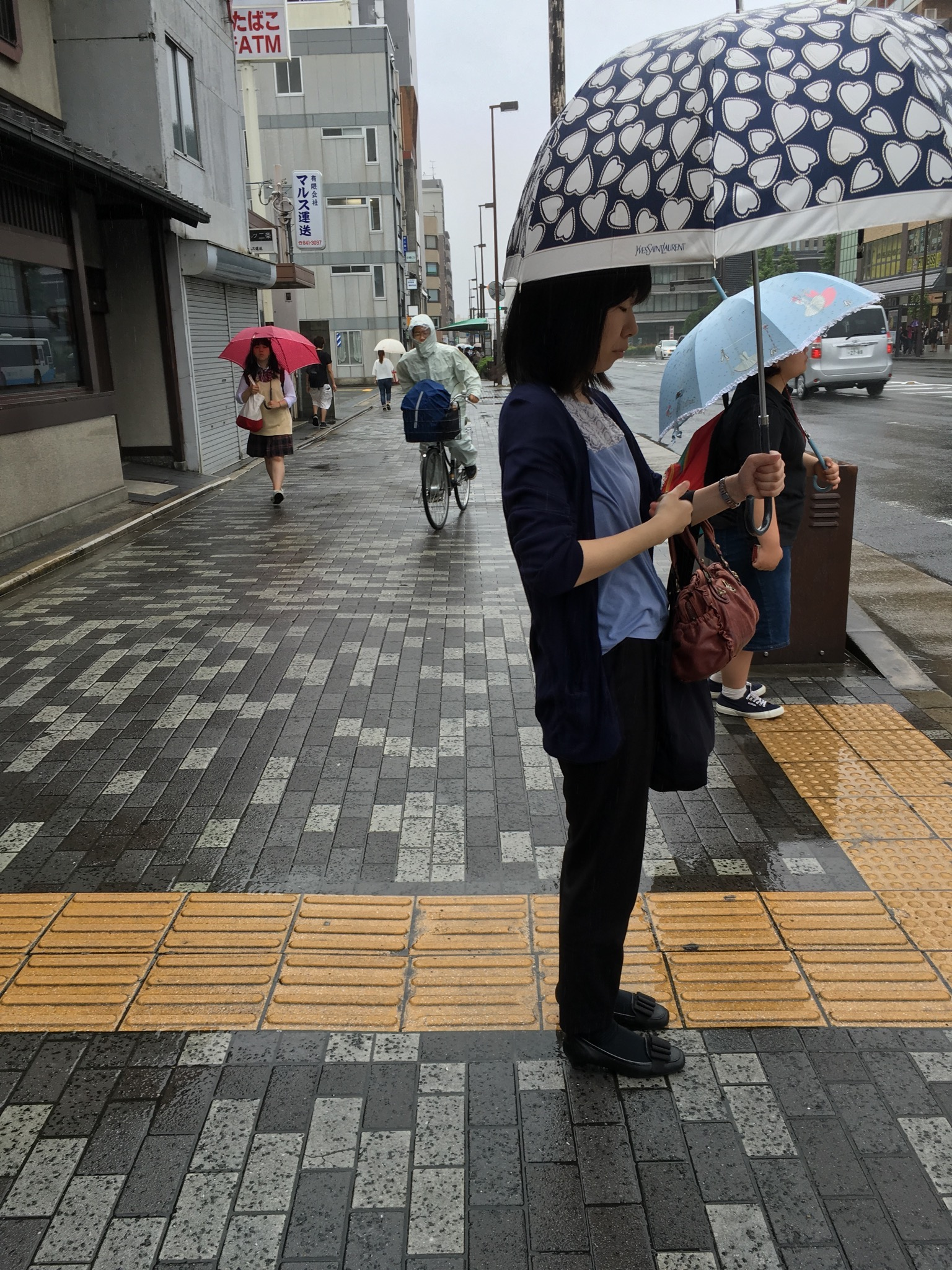 With rain comes umbrellas of many sizes and colours. They make negotiating the streets more challenging, especially with the bikes still weaving in-between the pedestrians. When they have umbrellas as well, such as in the image above, the space becomes even more limited.